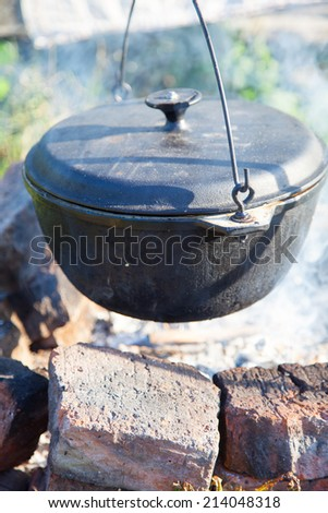 Pot on the fire outdoors - stock photo