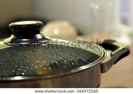 Pot with glass lid closeup to see water steam drops - stock photo