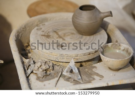 pot with pottery wheel and tool around - stock photo