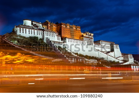 Potala palace in Tibet, China. Photo taken in after sunset, long exposure to capture the light trails of passing vehicle - stock photo