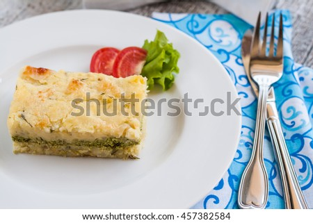 potato casserole with spinach on a plate and cutlery. - stock photo