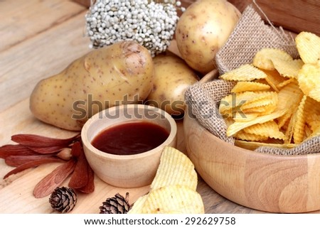 Potato chip and fresh potatoes on wood background - stock photo