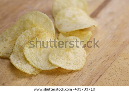 potato chips and salt on wooden background - stock photo