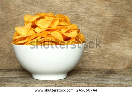 Potato chips bowl on a wooden background   - stock photo