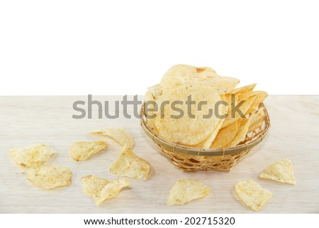 Potato chips in a basket on a wooden background. - stock photo
