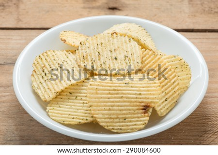 Potato chips in a white plate on wood background. - stock photo