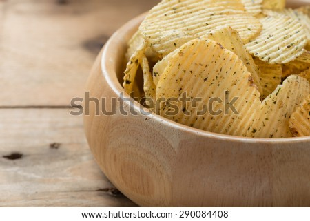 Potato chips in a wooden bowls, close-up - stock photo