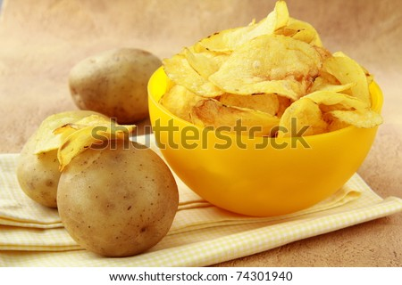 potato chips in a yellow cup, and fresh potato - stock photo