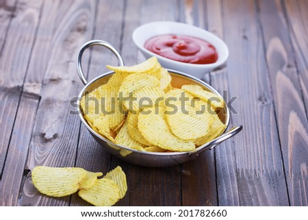 Potato chips in bowl on wooden background. Selective focus, horizontal. - stock photo