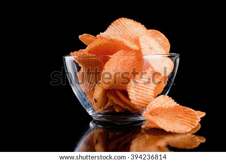 potato chips in glass bowl, isolated on background - stock photo