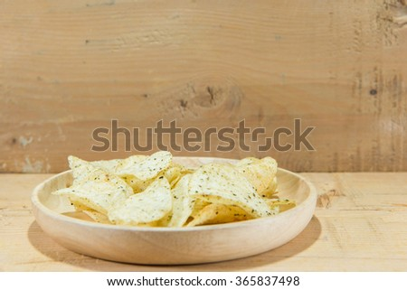 potato chips in wooden dish - stock photo