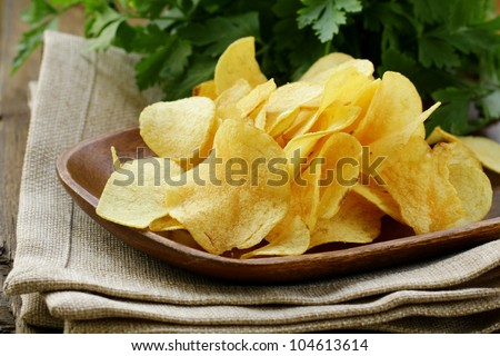 potato chips in wooden plate , on a wooden table - stock photo