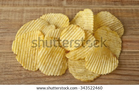 potato chips on a wooden table - stock photo