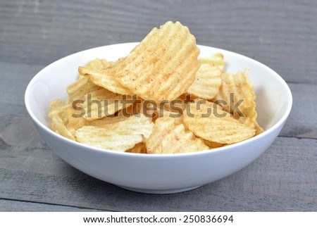 Potato Chips On Bowl With Wooden Background - stock photo