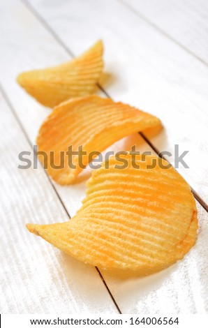 Potato chips on the white wooden plank table - stock photo