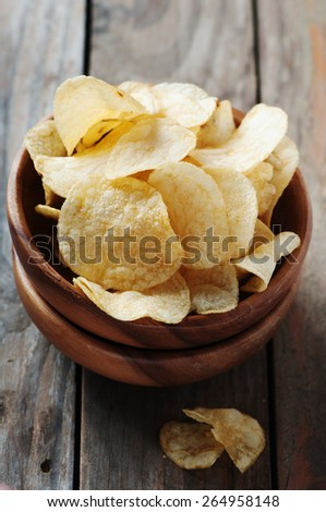 Potato chips on the wooden table, selective table - stock photo