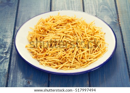 potato chips on white plate on wooden background