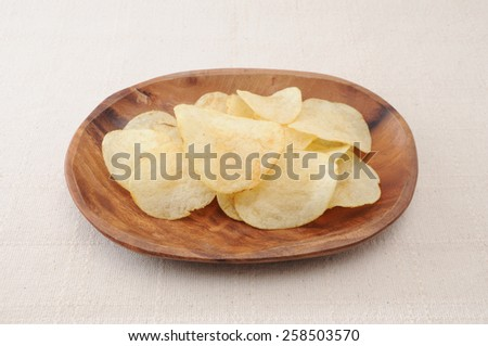 potato chips on wood plate on table cloth - stock photo