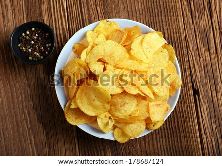 Potato chips on wooden background - stock photo