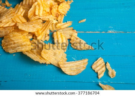 potato chips scattered on a blue wooden table