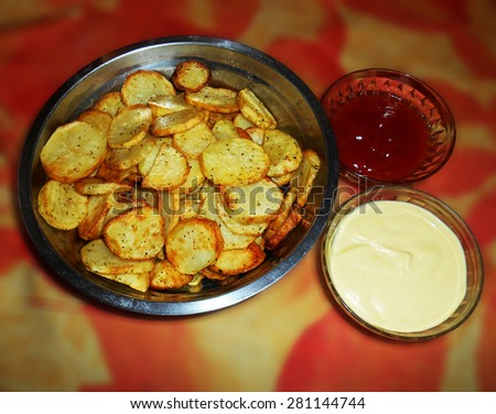 Potato chips with ketchup and mustard sauce on blurred background  - stock photo