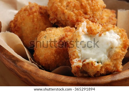 Potato croquettes  (mashed potatoes seasoned with fresh chives;  breaded and deep fried).  Macro with shallow dof.  Selective focus on opened croquette. - stock photo