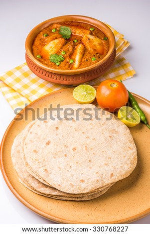 potato curry or aalu masala or aaloo masala with green peas, served with indian bread / roti / chapati / naan / fulka / phulka