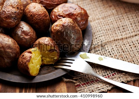 Potato food . Baked potatoes in a plate on a wooden rustic table. - stock photo