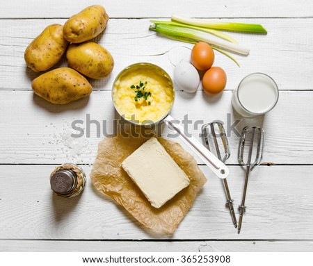 Potato food . Cooking mashed potatoes ingredients: potatoes, milk, eggs, butter and other on a white wooden table. Top view - stock photo