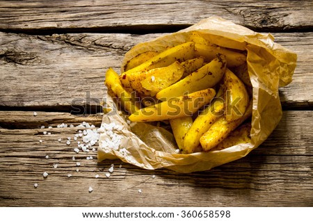 Potato food . Fries with spices and salt on wooden background - stock photo