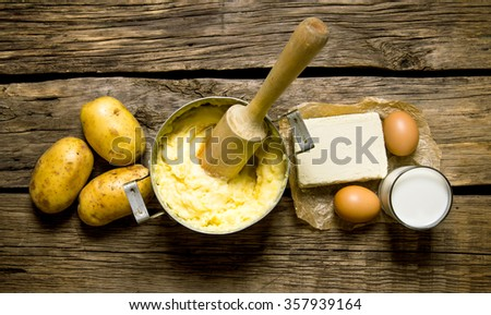 Potato food . Ingredients for mashed potatoes - eggs, milk, butter and potatoes on wooden background. Top view - stock photo