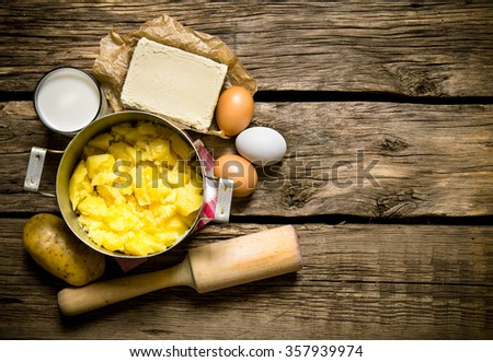 Potato food . Ingredients for mashed potatoes - eggs, milk, butter and potatoes on wooden background. Free space for text. Top view - stock photo