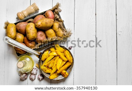 Potato food . The concept of baked potatoes in a skillet with spices on a white wooden table. Free space for text. Top view - stock photo