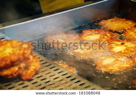 Potato fritters being cooked in a Vending Stall at a Christmas Market - stock photo