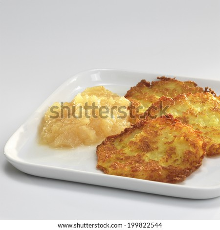 Potato fritters with apple sauce on plate - stock photo