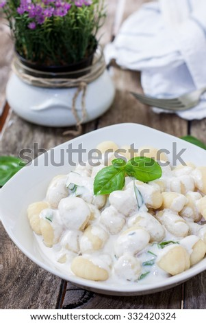 potato gnocchi pasta with cheese sauce and basil - stock photo