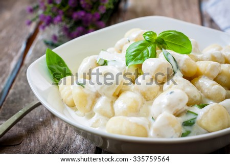 potato gnocchi pasta with cheese sauce and basil