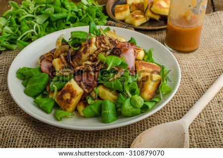 Potato gnocchi with summer salad, bacon and fried onions. Gnocchi boiled and then fried on pan for golden crispy - stock photo