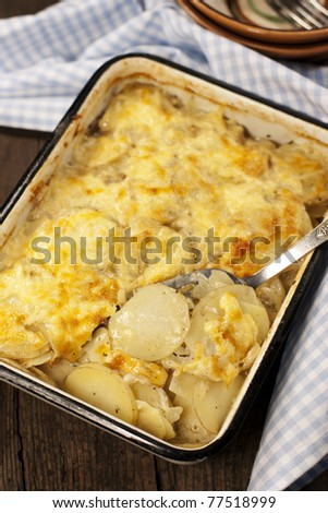 Potato gratin dauphinoise in the pan on rustic background - stock photo