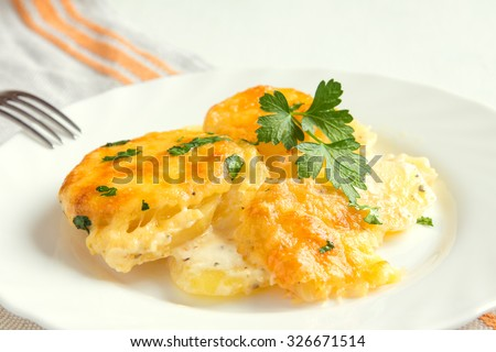 Potato gratin with cream, cheese and parsley on white plate - stock photo
