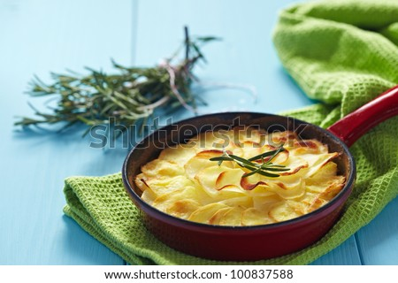 Potato gratin with rosemary in a small red pan - stock photo