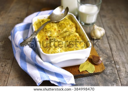Potato gratine in a baking form on rustic background. - stock photo