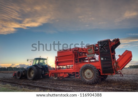 Potato harvester and tractor - stock photo