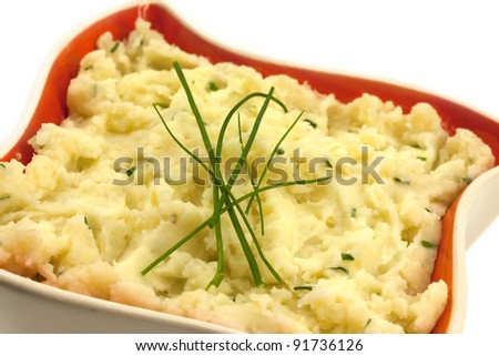 Potato mash with chives in a orange retro bowl