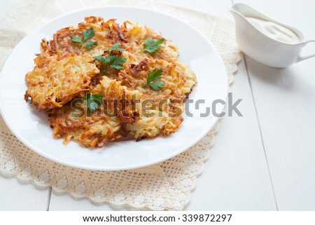 Potato pancaces or latke traditional Hanukkah celebration food with sour cream on white rustic background. Vegan organic meal. Natural light