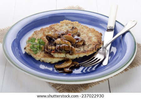 potato pancake with mushroom, onion, parsley and sauce on a blue plate - stock photo