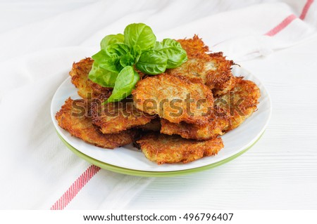Potato pancakes on a plate decorated with basil leaves