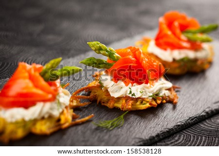 Potato pancakes topped with smoked salmon,asparagus and sour cream for holiday - stock photo