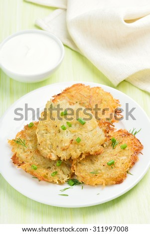 Potato pancakes with green onion and dill on white plate