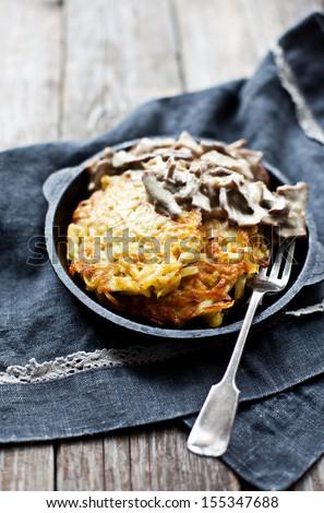 Potato pancakes with mushroom sauce - stock photo